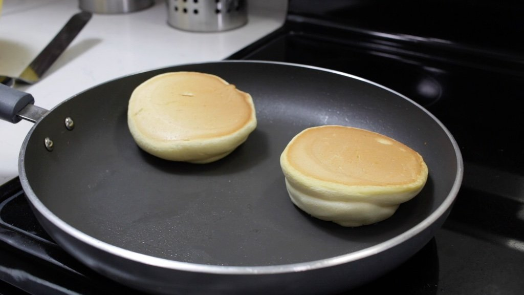 Two cooking souffle pancakes in a skillet on a stovetop burner.