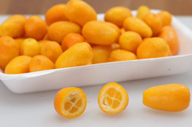 Pile of kumquats in white plate.