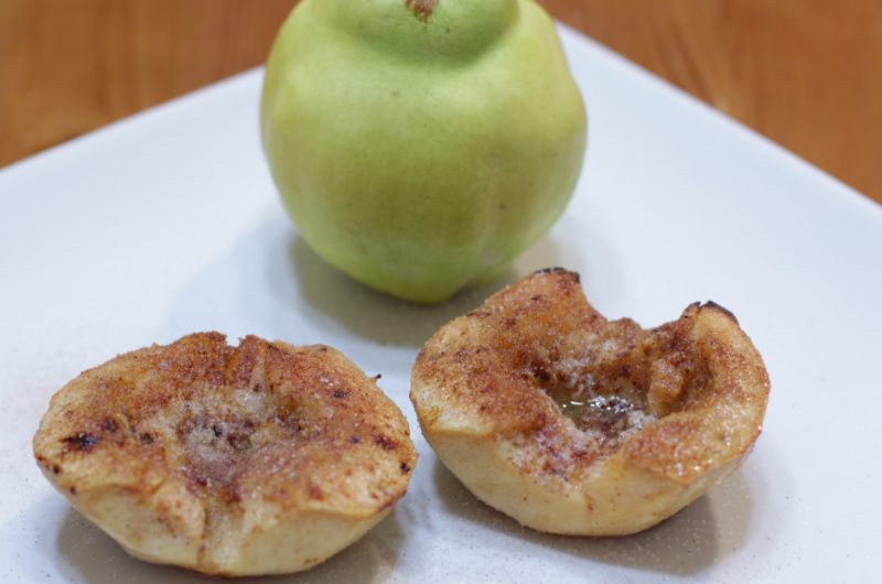 Quince fruit next to two slices of baked quince on a white plate