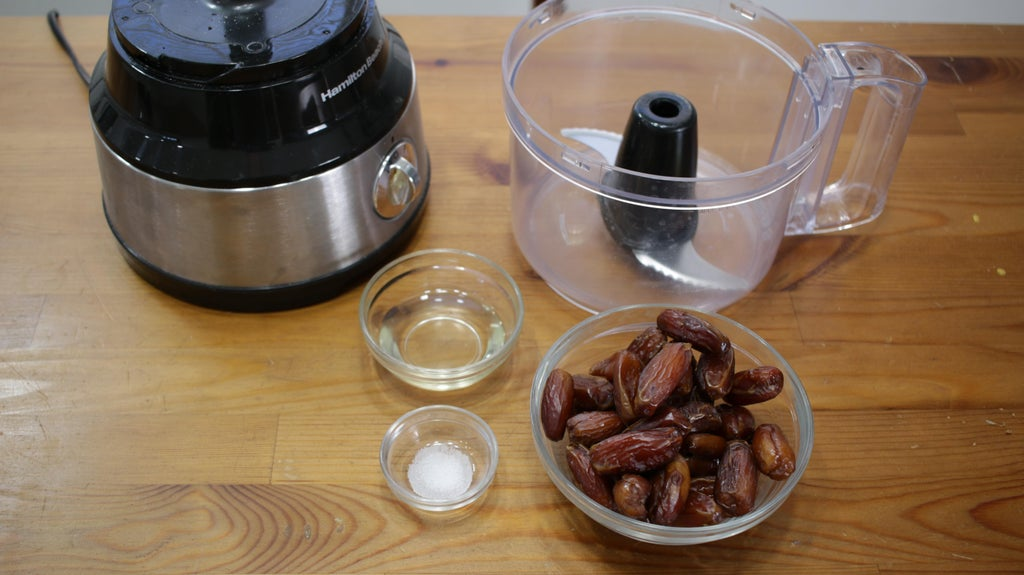 A glass bowl filled with dates and two small bowls of salt and coconut oil on a wooden table next to a food processor.