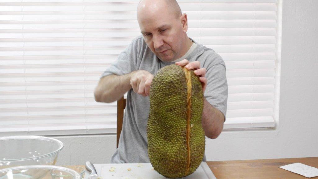 Man cutting a jackfruit in half lengthwise