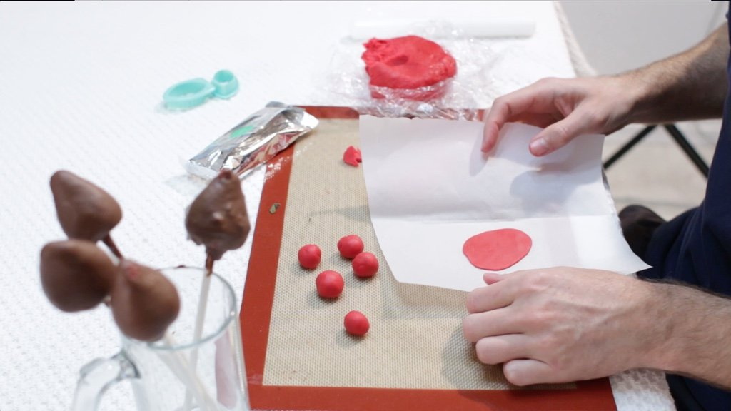 Red fondant rose petal on a piece of parchment paper.