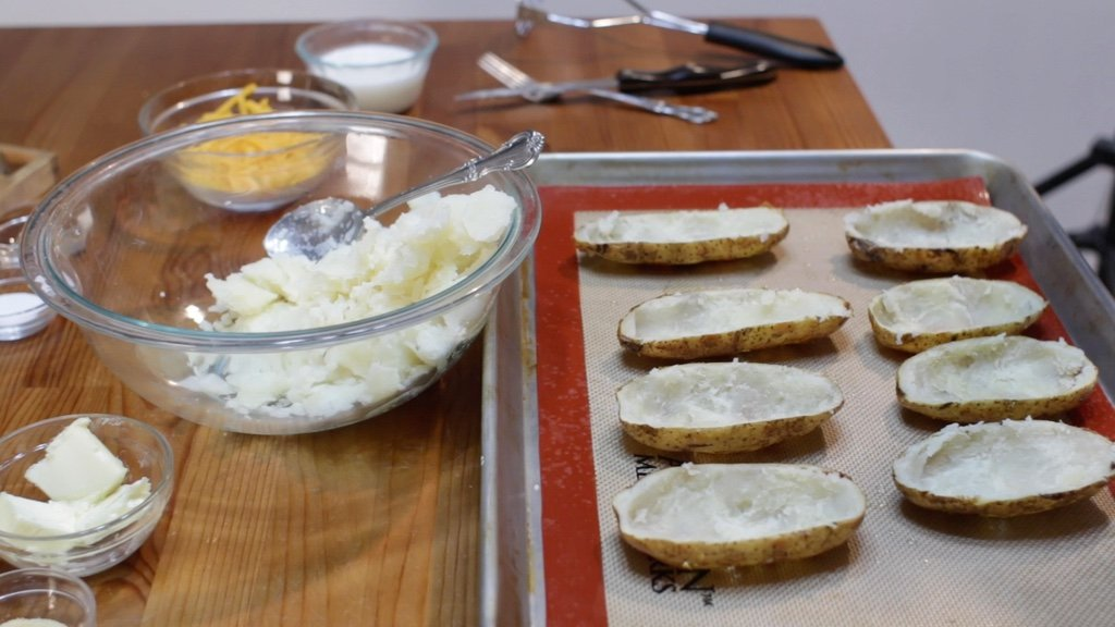Scooped potato skins next to a bowl of baked potato filling.