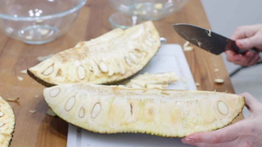 Sliced open jackfruit on a cutting board.