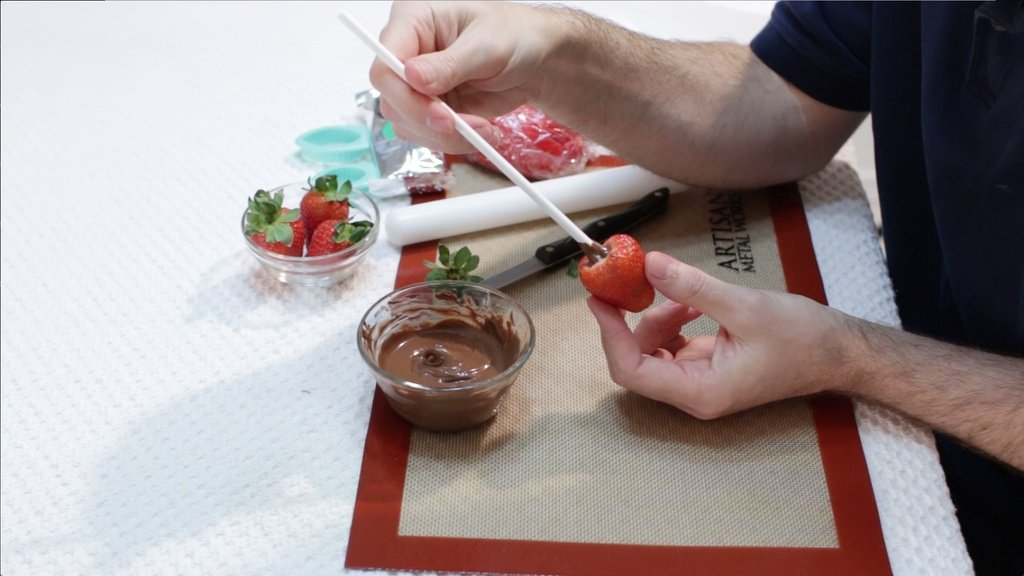 Hand sticking a treat stick in chocolate and into a strawberry