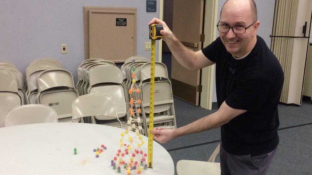 Guy measuring a gumdrop tower with a tape measure.