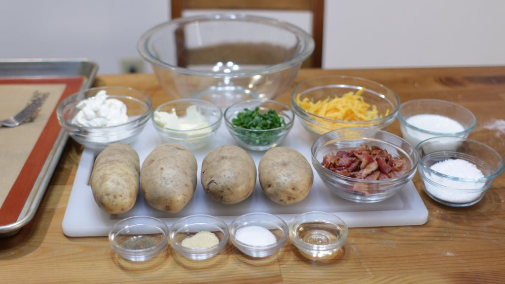 Potatoes and other ingredients in glass bowls on top of a wooden table.