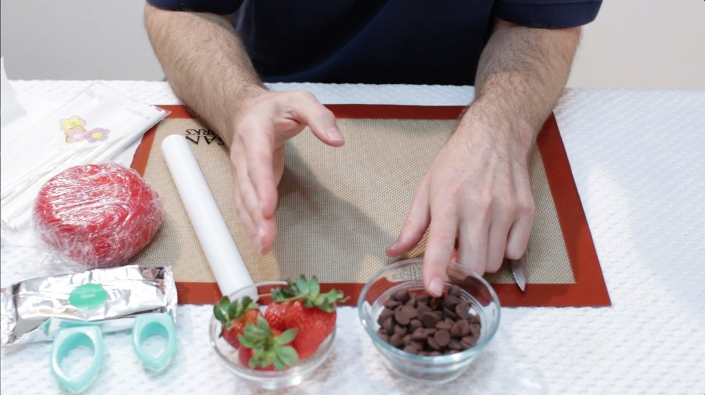 Hands pointing at a glass bowl of chocolate chips and strawberries.