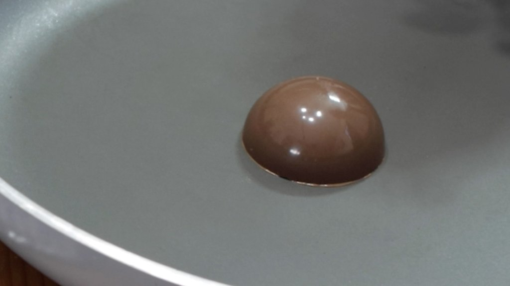 Half ball of chocolate on a gray skillet
