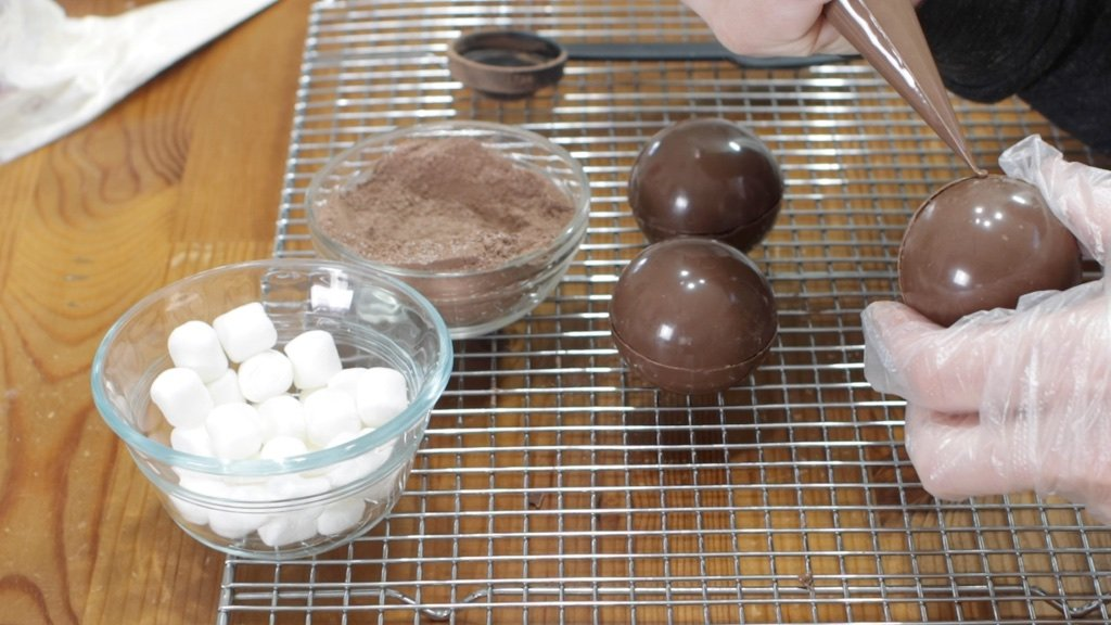 Hand piping melted chocolate around the equator of a hot chocolate bomb