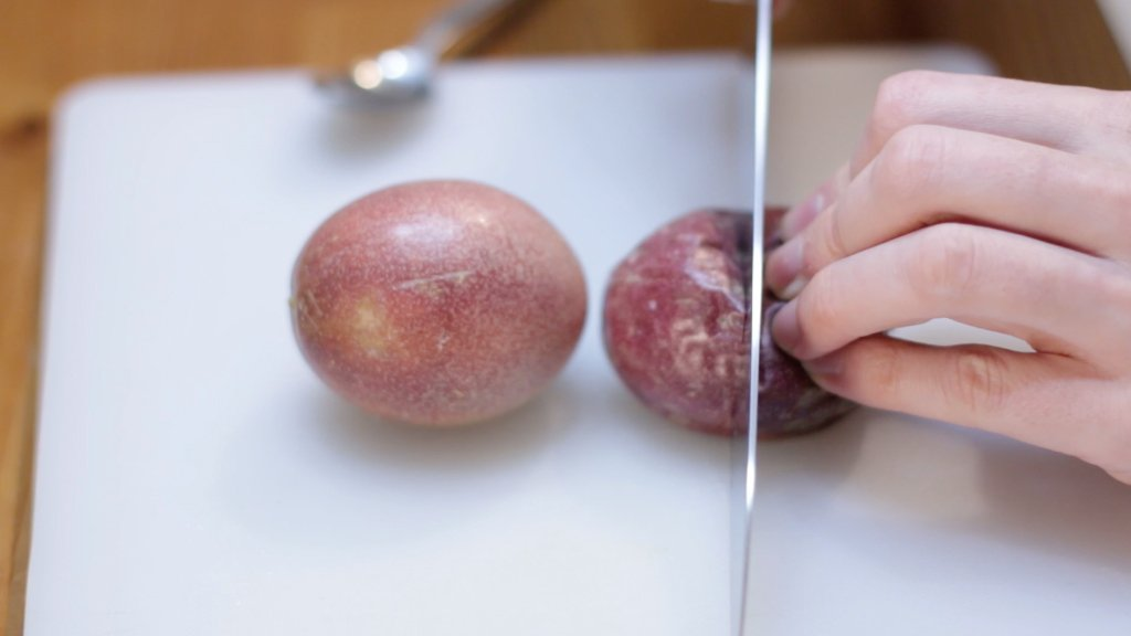 Knife cutting a passion fruit in half.