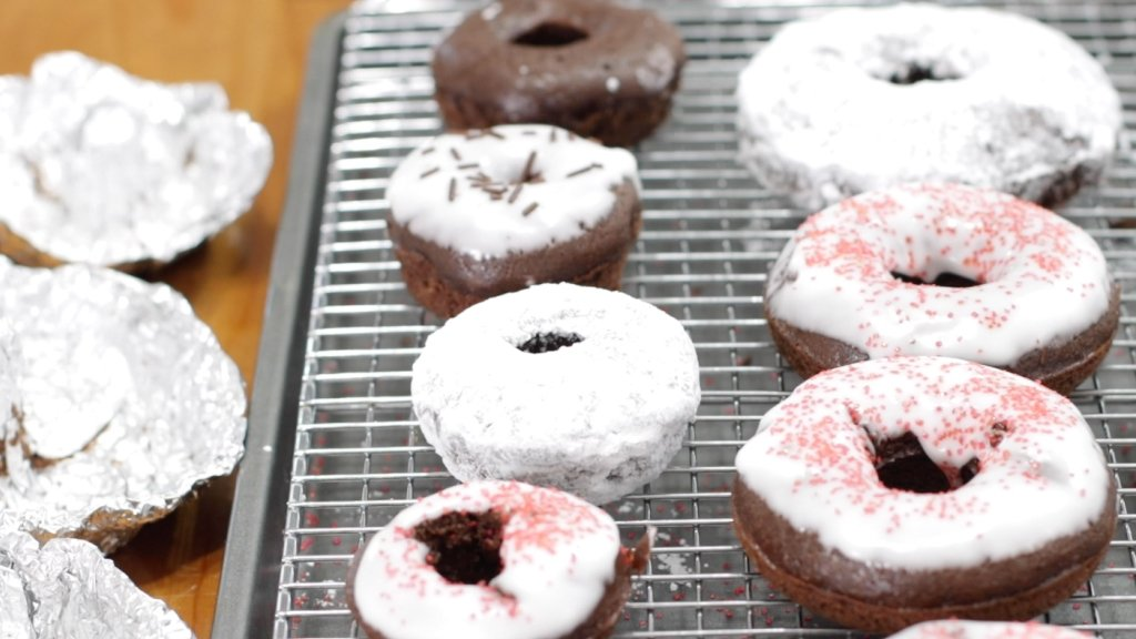 Freshly baked homemade cake donuts on a wire rack.