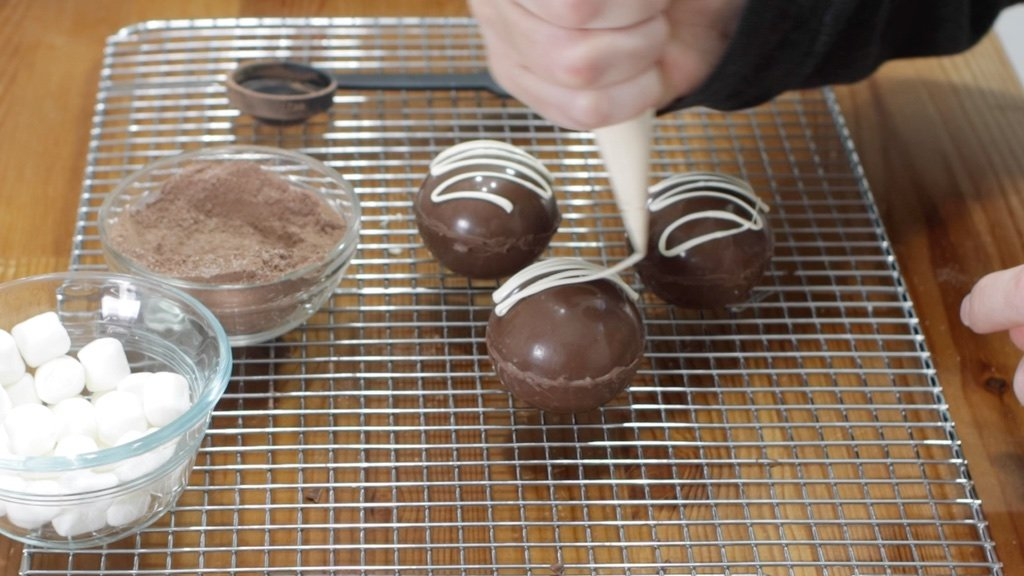Hand drizzling white chocolate over a hot chocolate bomb