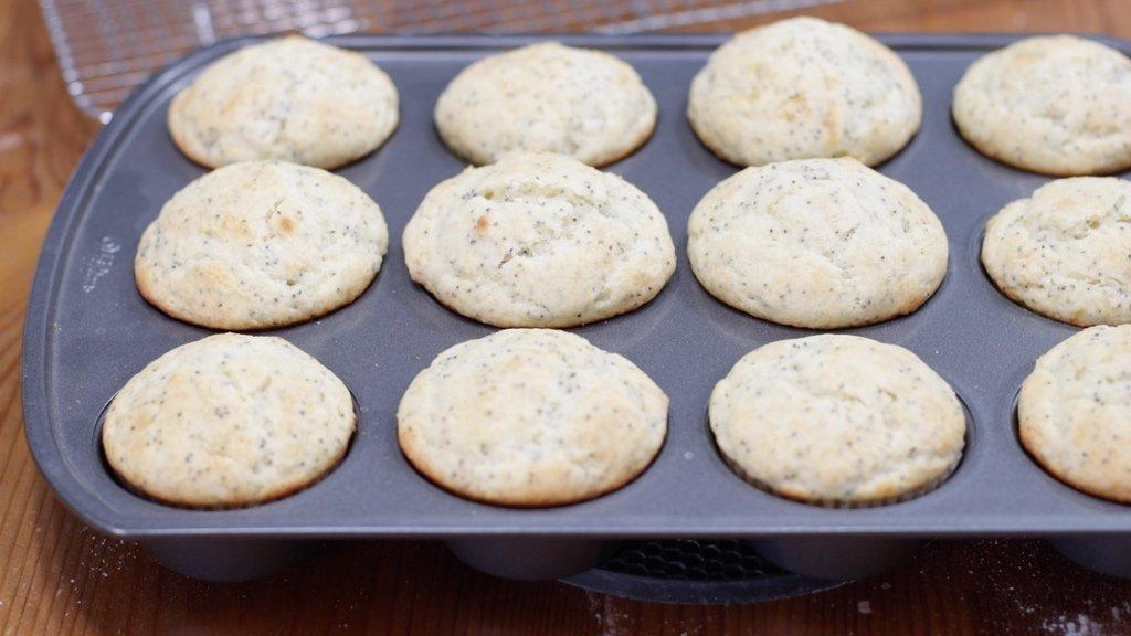 Freshly baked homemade lemon poppy seed muffins still in the pan.