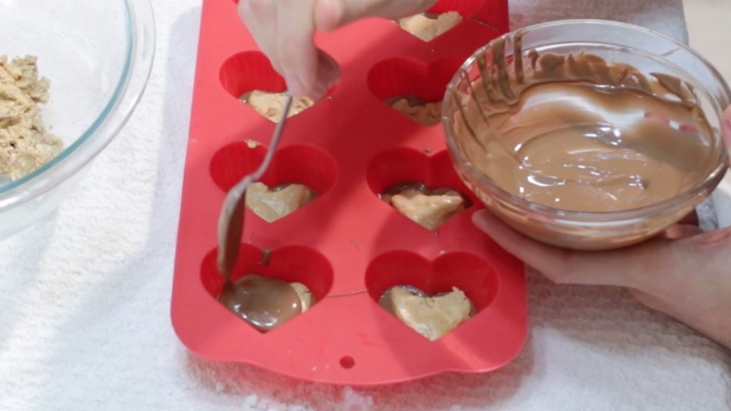 Hand with spoon add melted chocolate over peanut butter cups in a red silicone heart mold.