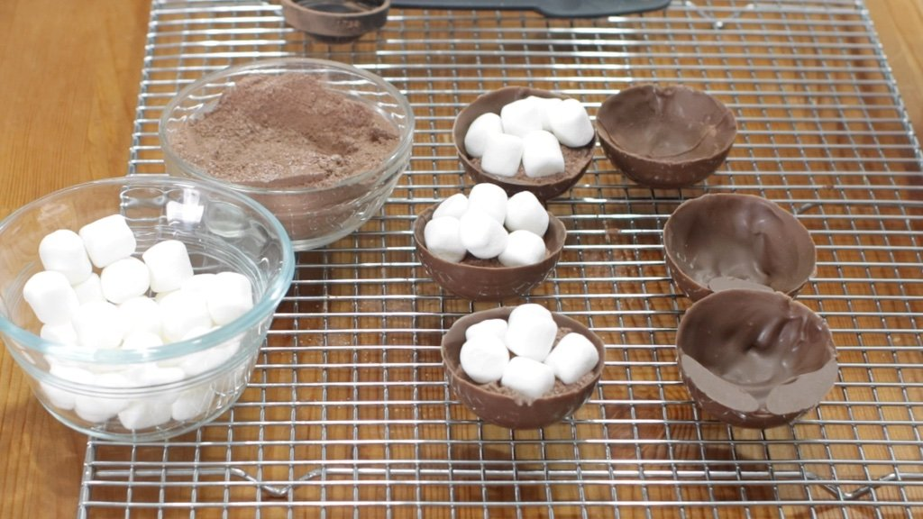 Hot chocolate bombs filled with hot cocoa mix and mini marshmallows on a wire rack