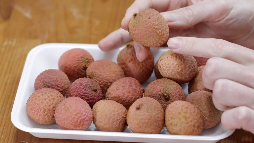 A pile of lychee on a white plate on a wooden table.