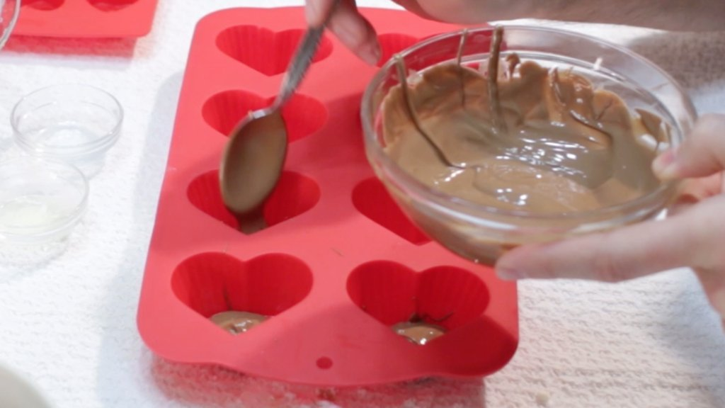 Hand holding a glass bowl of melted milk chocolate pouring it into a heart shaped mold.