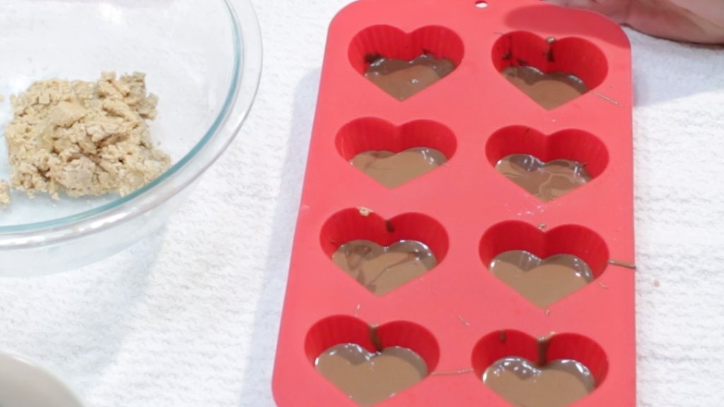 Peanut butter cup hearts in red silicone mold ready to go in the fridge