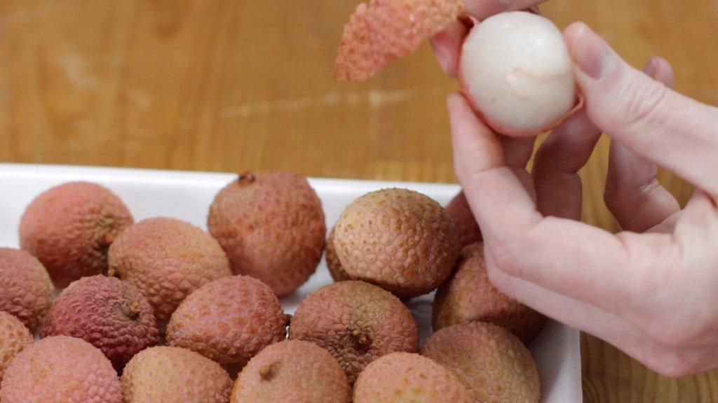 Hand peeling a lychee