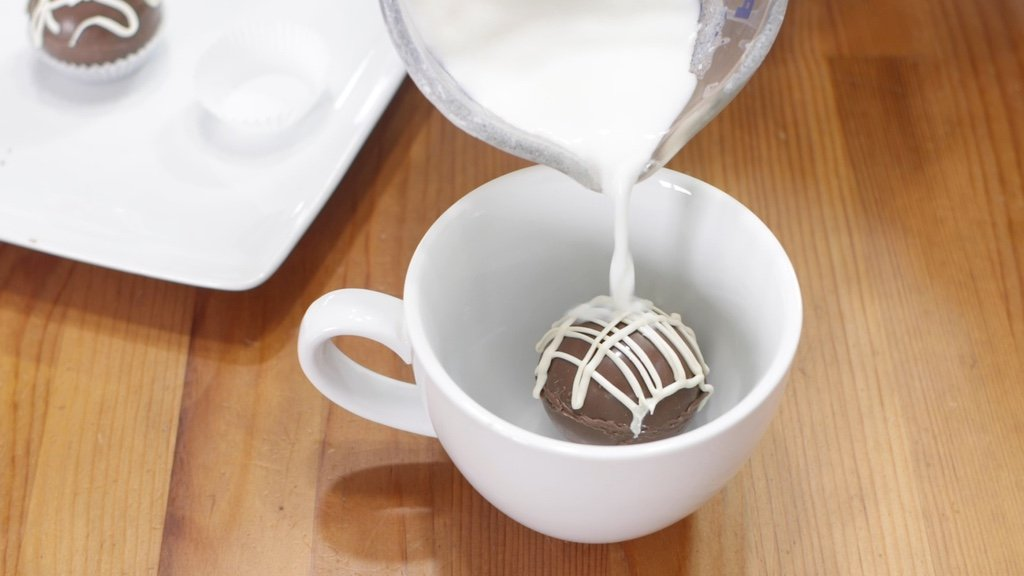 Cup pouring hot milk over a hot chocolate bomb in a white mug.
