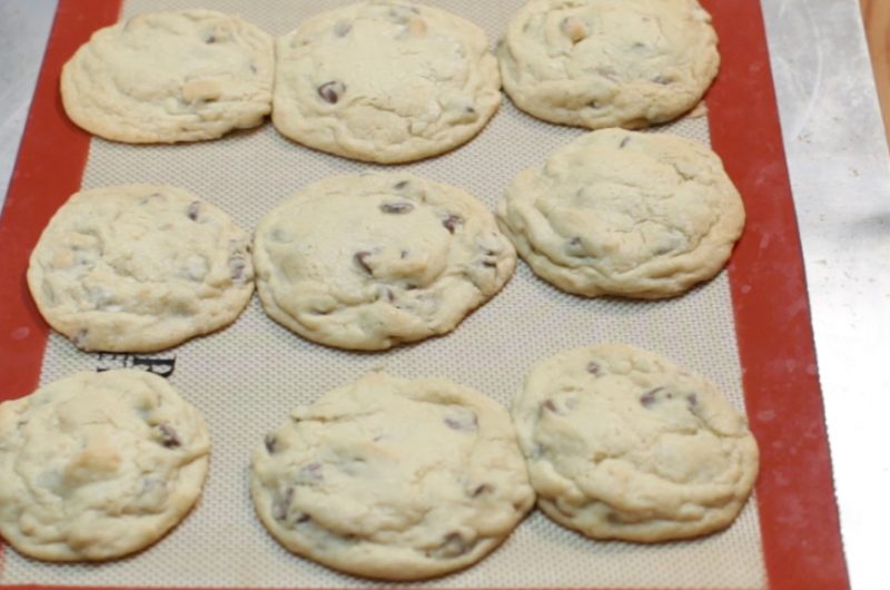 red silicone baking mat with chocolate chip cookies on it