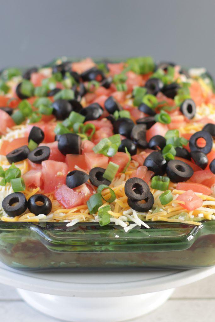 Seven layer bean dip in a green glass dish.
