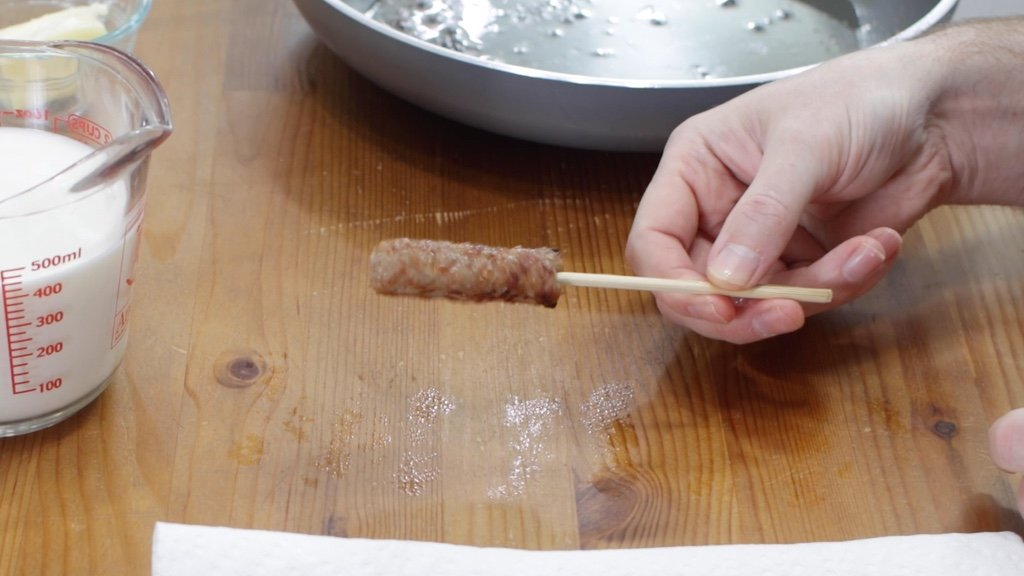 Hand holding a cooked sausage on a stick