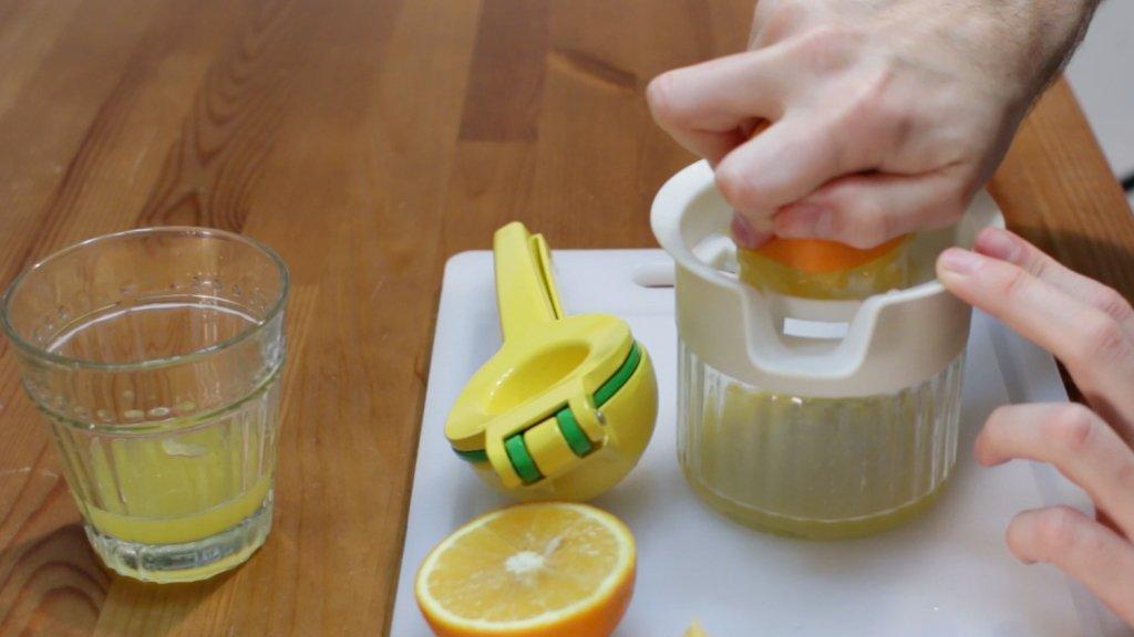 Hand juicing an orange on a manual juicer.