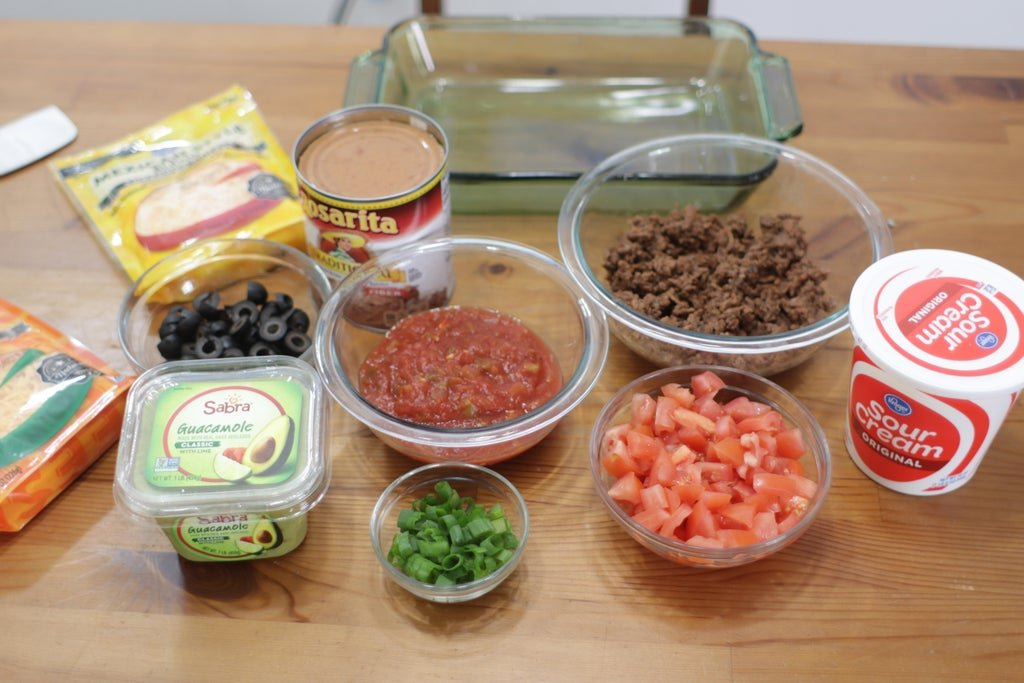 Several bean dip ingredients in glass bowls on wooden table.