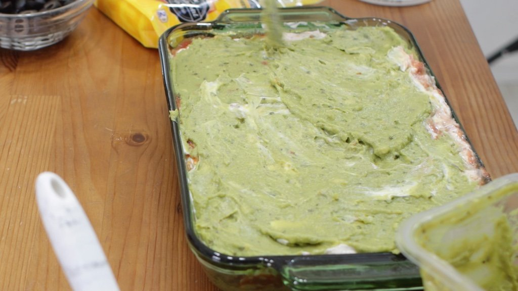 Guacamole being spread on to a bean dip.