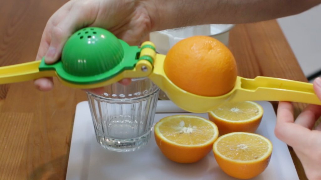 Zulay manual citrus press juicer with a large half cut orange on it.