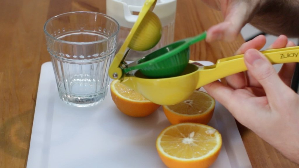 Hand holding open a Zulay manual citrus press